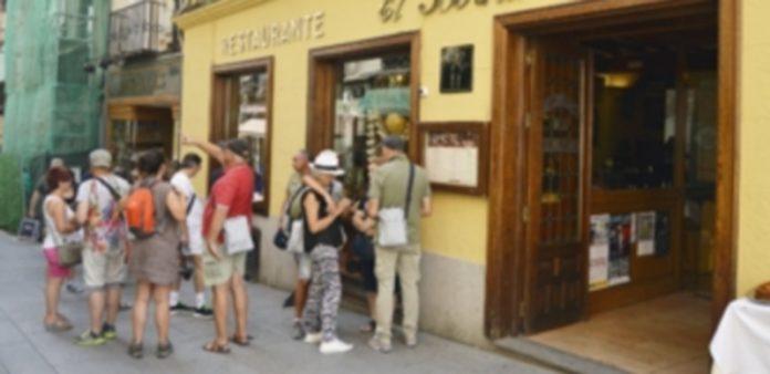 Un grupo de turistas consulta la oferta gastronómica de uno de los restaurantes de la capital segoviana. / Cristina Yusta