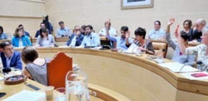 Los concejales del Gobierno municipal socialista alzan sus brazos durante la votación del pliego del transporte urbano