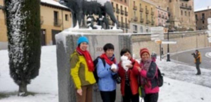 Un grupo de turistas orientales  posan con nieve en la mano frente a la estatua de la Loba Capitolina
