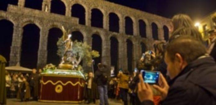 Un turista fotografía la imagen del paso de 'La Oración en el Huerto' de la cofradía de San Lorenzo a su paso por el Acueducto. / Kamarero