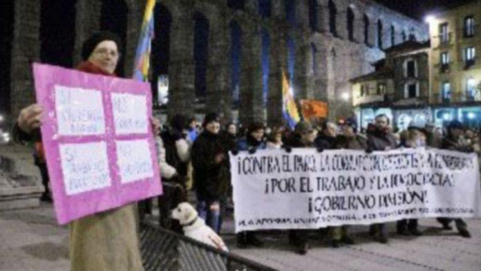 Cabeza de la manifestación que recorrió el centro de segovia y pancarta con las reivindicaciones de este 23F. / Juan Martín