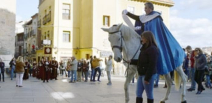 Uno de los heraldos a caballo da lectura al anuncio del pregón en la Calle Real