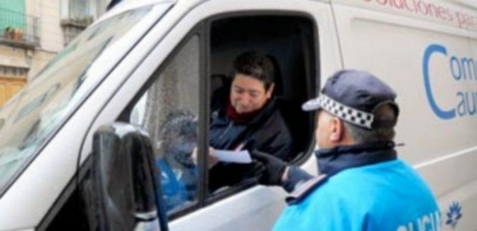 Un agente entrega al conductor de un vehículo información de los nuevos horarios de carga y descarga. / Kamarero