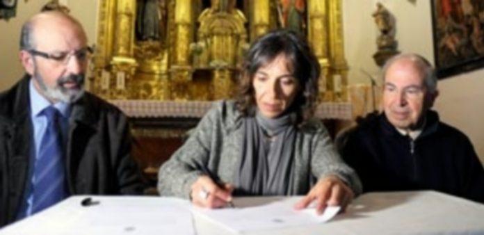 Martín estampa su firma en presencia del presidente de la Junta de Cofradías y del párroco de Santo Tomás./ Kamarero