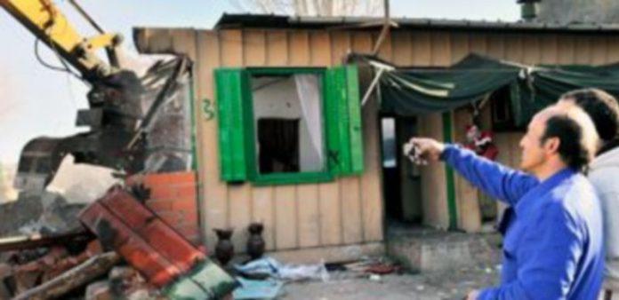 Uno de los residentes recoge una instantánea del derribo con la cámara de un teléfono móvil. Última despedida a sus viviendas. / Kamarero