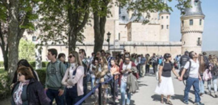 Fila de turistas para recoger la entrada de acceso al Alcázar en una de las jornadas centrales de la Semana Santa. / KAMARERO