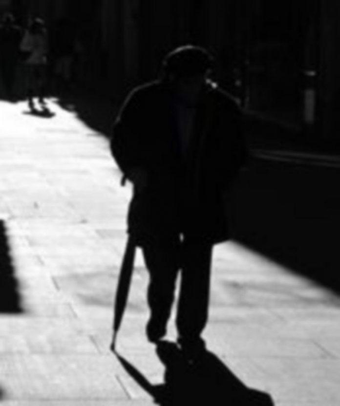 Un jubilado camina ayudándose de un paraguas por una calle de la capital segoviana. / Juan Martín