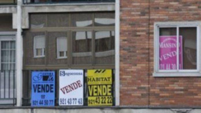 Carteles de cuatro agencias inmobiliarias indicando la venta de una vivienda en la capital segoviana. / Juan Martín
