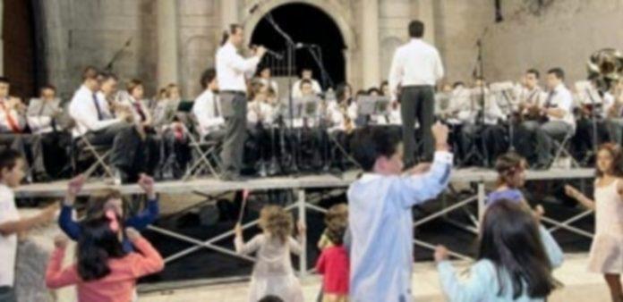 La Banda Municipal de Música con el pañuelo rojo al cuello e interpretando
