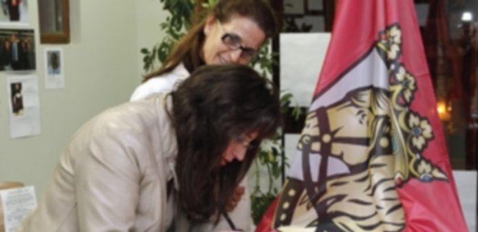 Dos vecinas de Cuéllar firman en la bandera oficial del municipio./ Gabriel Gómez