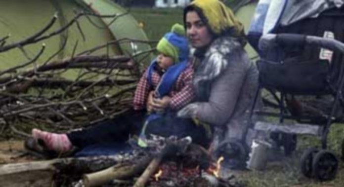Una mujer y su hijo intentan calentarse en el exterior de su tienda en el campo provisional de refugiados de Idomeni . / EFE