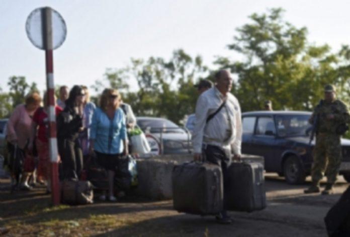 Varias personas cruzan el puesto de control de Zaytsevo en Ucrania. / EFE