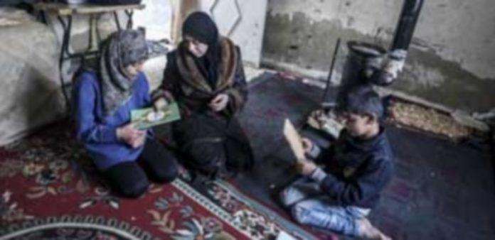 Una mujer ejerce de maestra con sus hijos en su casa del distrito de Al-Qaboon en la capital siria