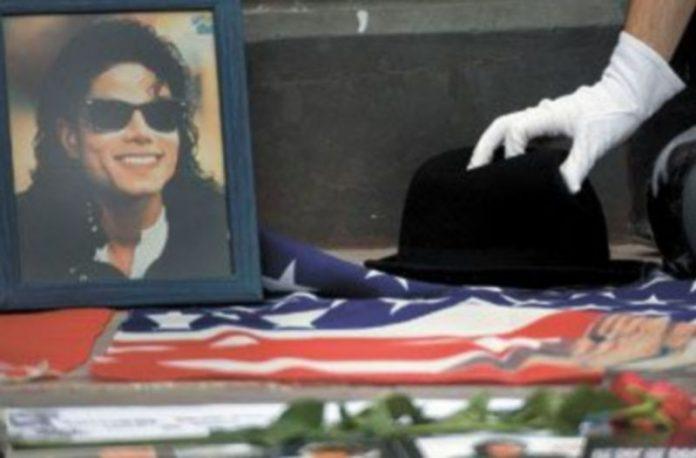 Un admirador de Michael Jackson deposita un sombrero junto a su foto durante un homenaje. / EFE