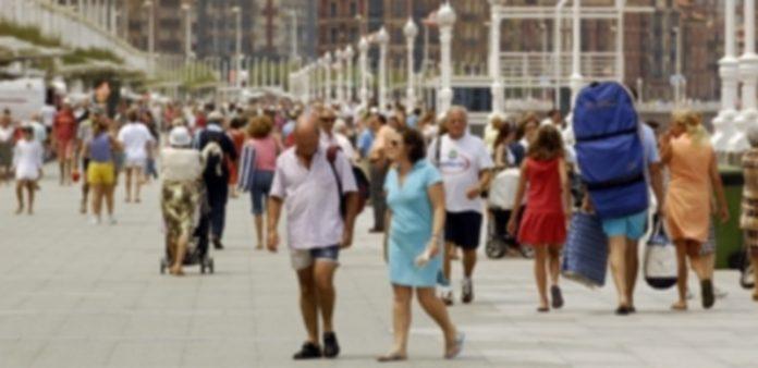 Numeroso turistas pasean por una de las avenidas más transitadas de la ciudad asturiana de Gijón. / EP