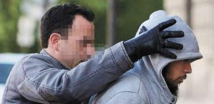 Un agente traslada a Alexandre a la Comisaría tras detenerle en la casa de un amigo