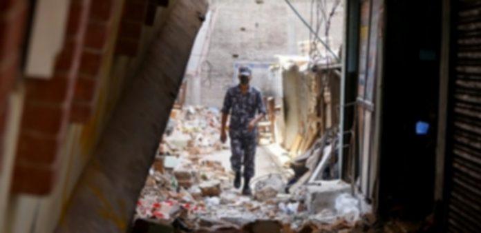Un soldado nepalí camina entre los restos de un edificio destrozado a consecuencia del terremoto en el país. / Efe