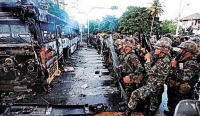 Soldados tailandeses toman posiciones frente a un autobús incendiado