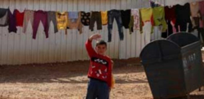 Un niño saluda desde un campamento de refugiados sirios ubicado en Jordania
