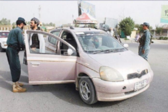 Varios oficiales de seguridad afganos cachean a algunas personas en la ciudad de Kandahar