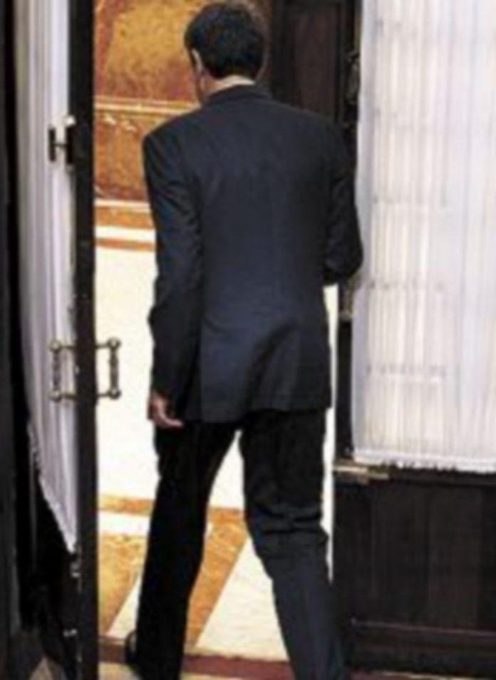 Zapatero sale por una puerta.