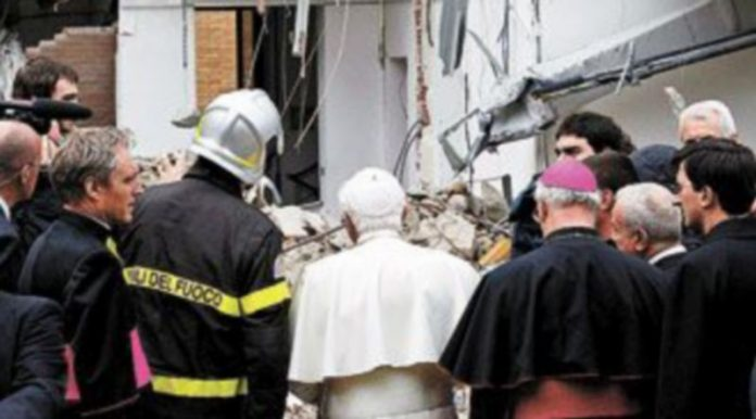 Benedicto XVI habla con un bombero durante su visita a L'Aquila. / A. DI MEO (efe)