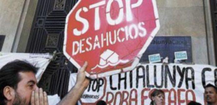 Un activista sostiene una pancarta como protesta de los desahucios. / A. Gea (Reuters)