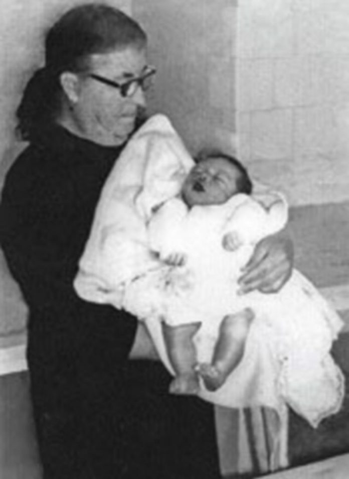 Una mujer sostiene a un bebé.