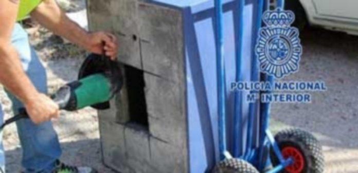 Un agente de la Policía Nacional junto a parte del material incautado durante el dispositivo. / E.P.