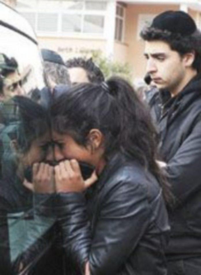 Una mujer llora sobre uno de los coches fúnebres. / Reuters