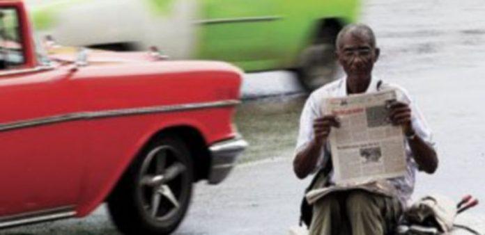 Un hombre lee en 'Granma' el texto que proclama la nueva normativa. / Reuters