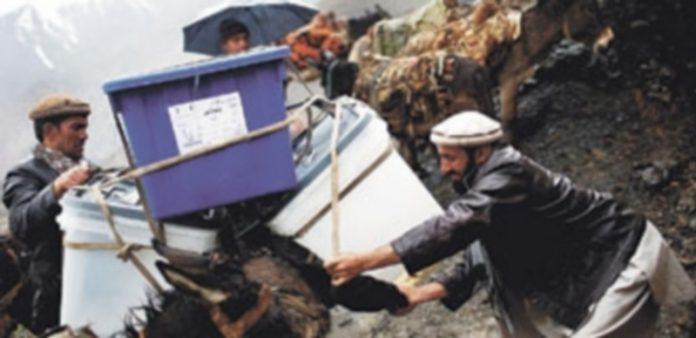 Dos hombres cargan sobre un burro las cajas donde se depositarán hoy las papeletas en los comicios. / Reuters