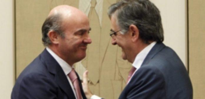Luis de Guindos saluda al nuevo presidente de la Comisión de Economía del Congreso