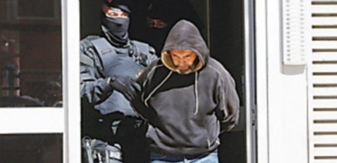 Mossos d'Esquadra custodian a una de las once personas que fueron detenidas en una operación contra el terrorismo. / Efe