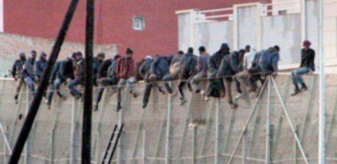 Unos treinta subsaharianos estuvieron varias horas encaramados en la valla. / EFE