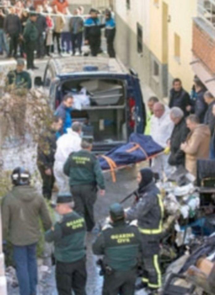 Efectivos de los servicios funerarios trasladan el cuerpo de uno de los fallecidos. / EFE