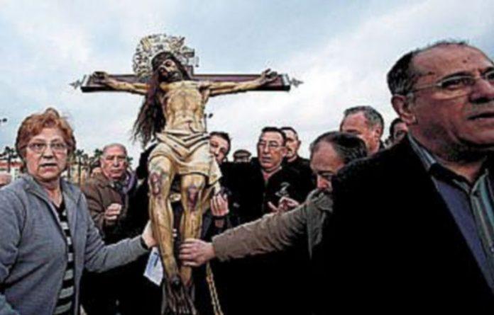 Los fieles tocan la figura del Santísimo Cristo del Salvador durante la Semana Santa Marinera de Valencia. /EFE