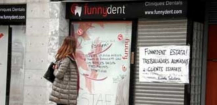 Una mujer lee la pancarta colocada en la puerta de una de las clínicas de FunnyDent en la localidad barcelonesa de Mataró. / Efe