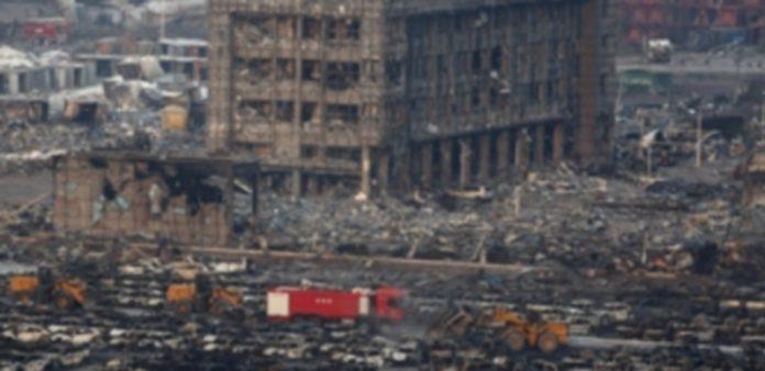 Miembros de los servicios de rescate trabajan en los vehículos y edificios quemados tras la explosión en Tianjin. / EFE