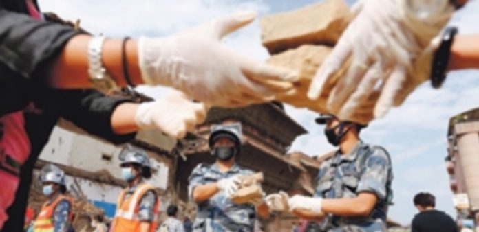 Voluntarios y miembros de equipos de rescate trabajan en la zona donde un templo se derrumbó tras el seísmo. / Efe