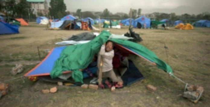 Un hombre intenta sostener su tienda contra la fuerza del viento en uno de los campamentos cercanos a Katmandú donde miles de personas se refugian. / EFE