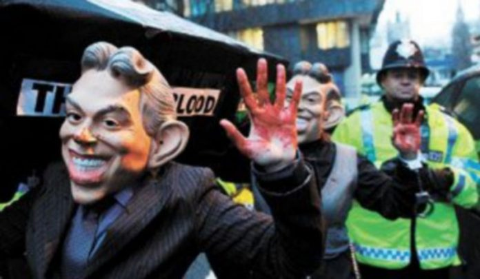 Manifestantes disfrazados de Blair son escoltados por la Policía frente al lugar de Londres donde se celebra la comisión sobre la invasión de Iraq. / EFE