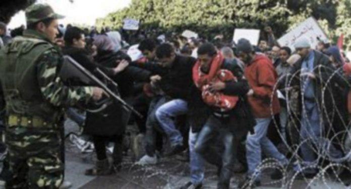 Centenares de manifestantes logran superar una barrera alambrada ante la pasividad de un soldado en la capital tunecina. / Efe