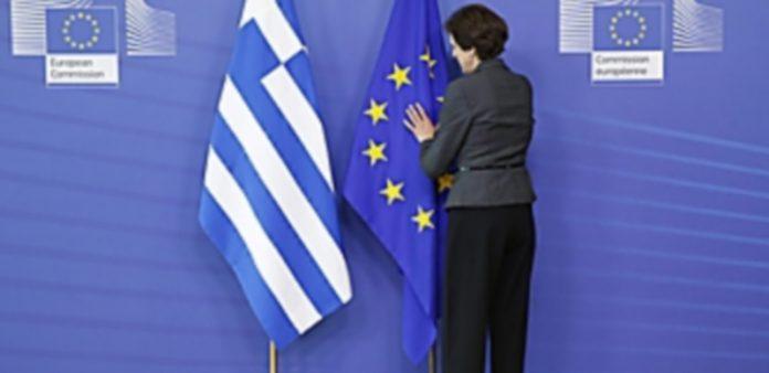 Una mujer arregla las banderas de Grecia y la Unión Europea en la sede de la UE en Bélgica