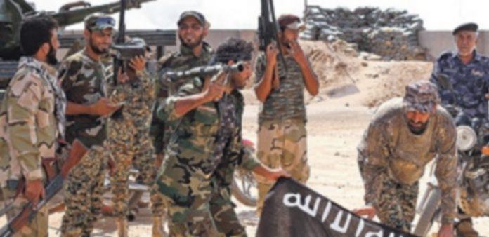 Varios componentes de  fuerzas de seguridad iraquíes sostienen armados una bandera del grupo Estado Islámico. / Efe
