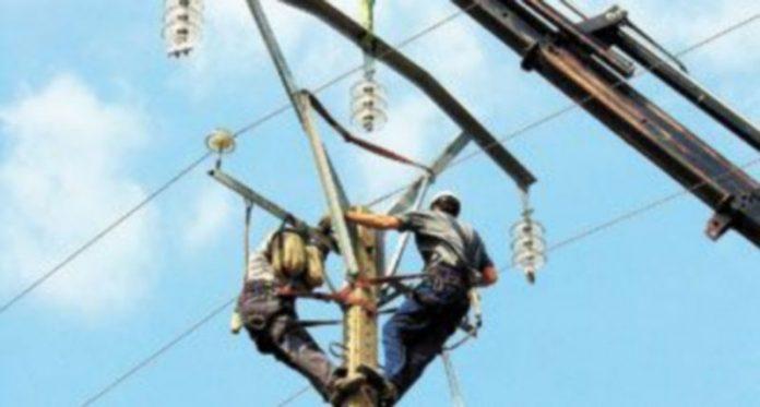 Dos operarios de la energía arreglan una torre de alta tensión.