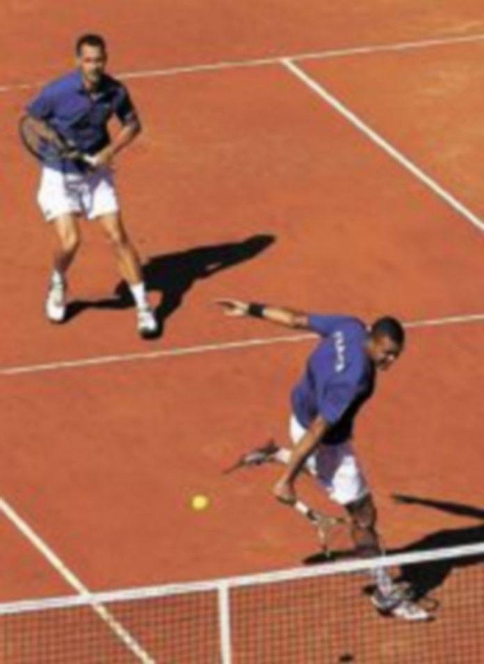 El 'número uno' francés remacha ante la mirada de Llodra. / Reuters.