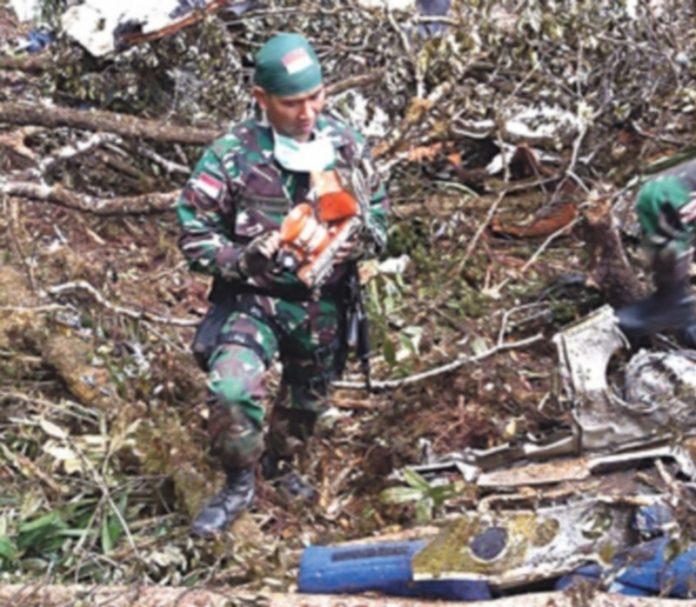 Un miembro del equipo de rescate indonesio sostiene la caja negra del avión siniestrado en Papúa hace tres días. / EFE