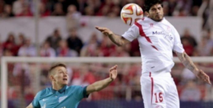 El sevillista Éver Banega salta a por el balón ante la mirada de Oleg Shatov. / EFE