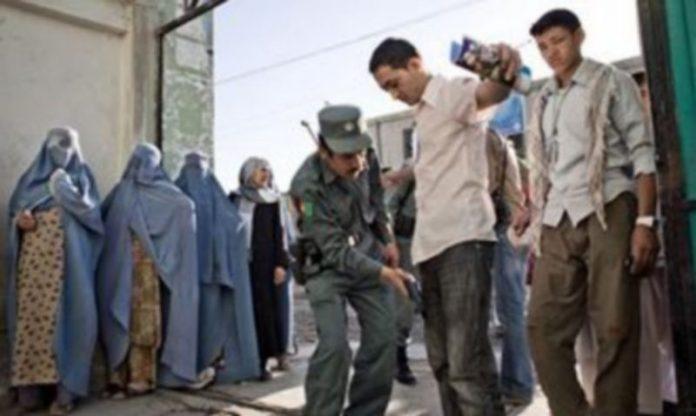 Un policía afgano requisa a los votantes en un centro electoral hoy